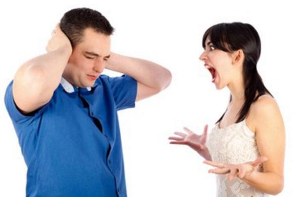 Женщина кричит на мужчину. Он закрывает уши руками