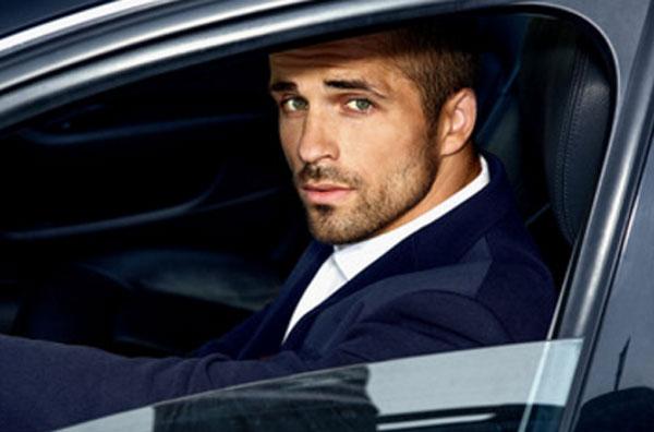 Красивый и ухоженный парень сидит за рулем автомобиля