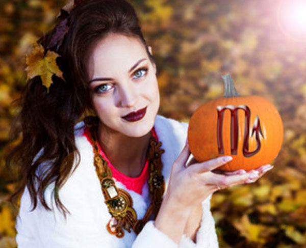 Девушка в осеннем парке. Держит в руках тыкву, на которой нарисован знак Скорпиона