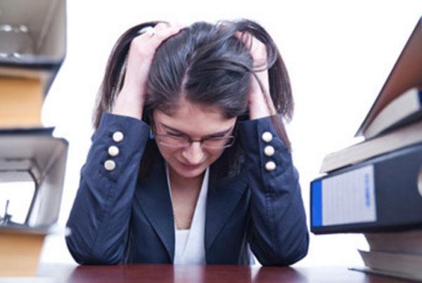 Женщина вся на нервах. Сидит за столом, на нем папки с документами