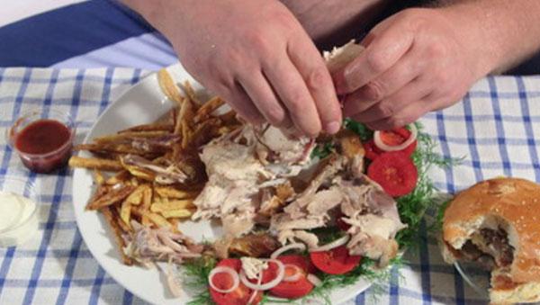 Большая тарелка с вредной едой и надкусанный бургер на столе