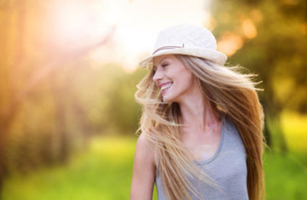 Счастливая девушка в шляпке прогуливается по улице