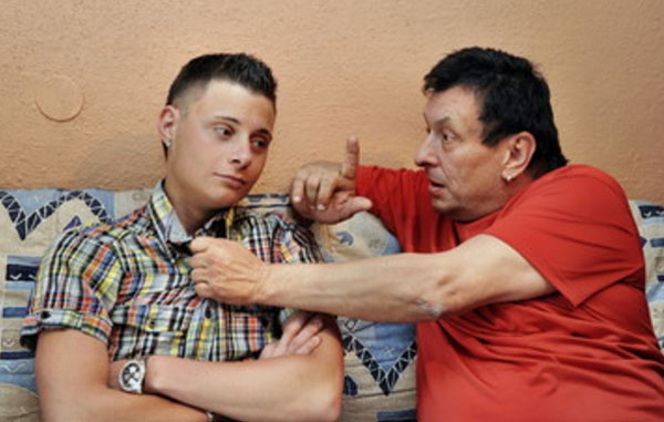 Отец схватил сына за воротник и что-то ему доказывает