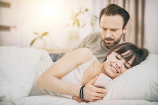 Муж и жена в кровати. Она смотрит в телефон и улыбается. Мужчина насторожен, пытается увидеть, что там происходит