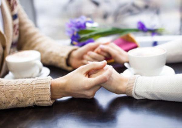 Руки девушки и парня. Пара сидит за столом напротив друг друга, на котором стоят чашечки и держатся за руки