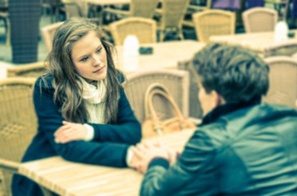 Парень с девушкой сидят за столиком в кафе. молодой человек просит прощения