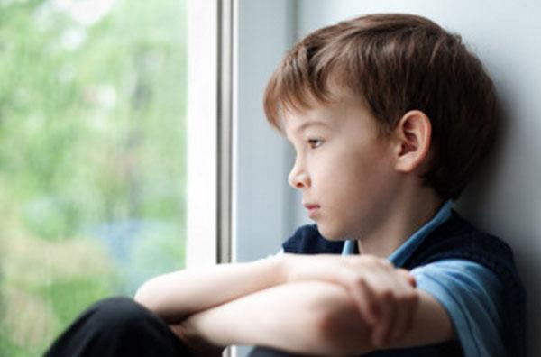 Печальный ребенок сидит на окне