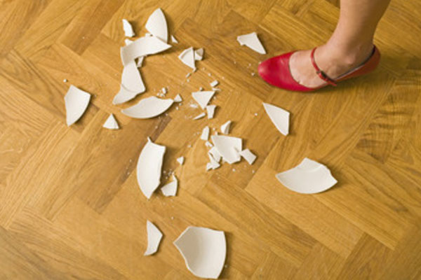Разбитая тарелка на полу и ножка девушки