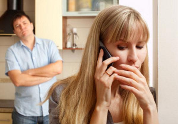 Женщина говорит по телефону, прикрываясь рукой. Мужчина стоит сзади. Начинает нервничать