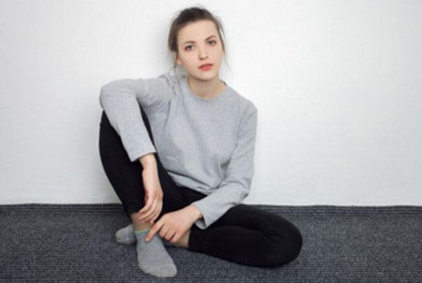 Девушка сидит на полу. У нее грустное выражение лица