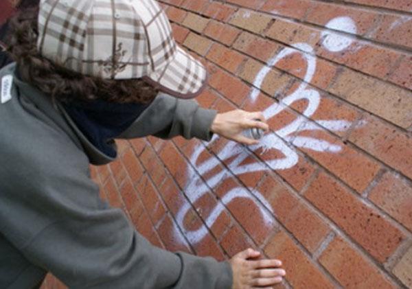 Ребенок в кепке и завязанным лицом рисует граффити на стене