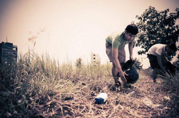 Мужчина собирают мусор на траве