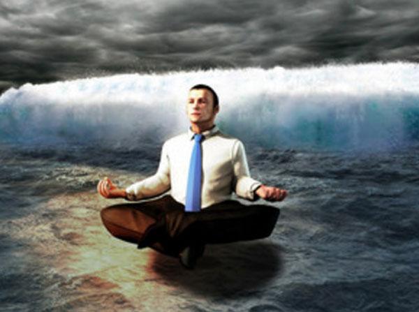 Спокойный мужчина сидит в позе лотоса над водой. Сзади надвигается цунами