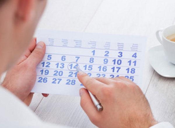 Мужчина обводит ручкой число в календаре