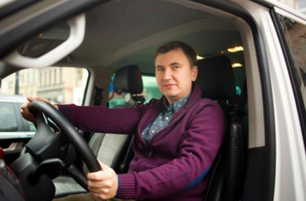 Веселый мужчина сидит за рулем машины