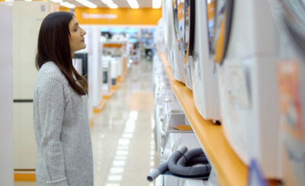 Женщина стоит в магазине перед стиральными машинками. Она расстроена