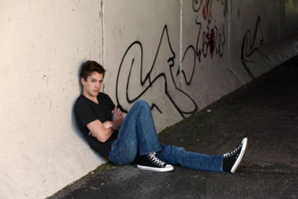 Одинокий парень сидит на земле в подземном переходе