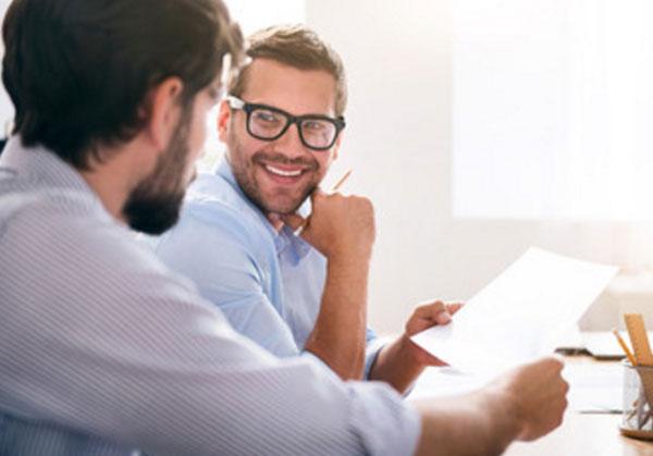 Два мужчины на работе держатся за один листок бумаги