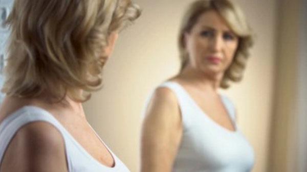 Женщина смотрит на себя в зеркало