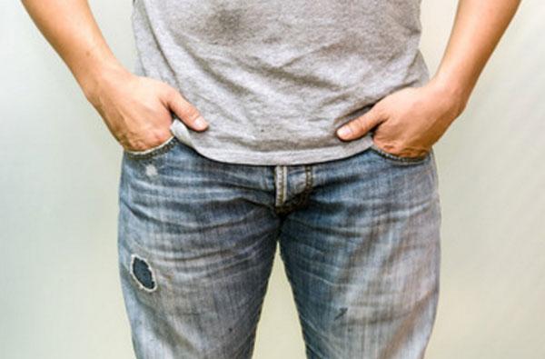 Мужчина с руками, спрятанными в карманы джинс. Большие пальцы высунуты наружу
