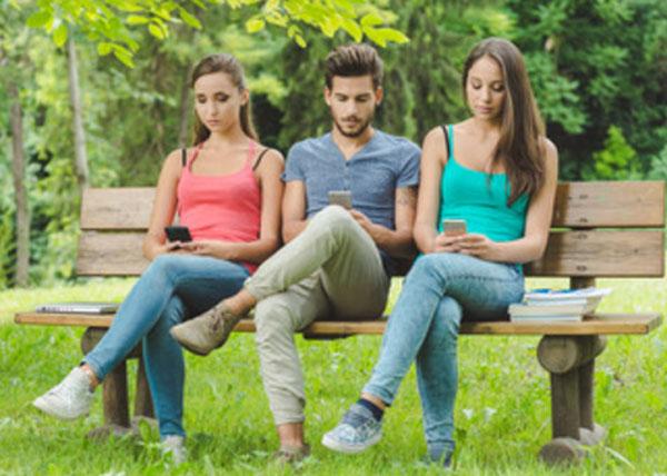 Две девушки и парень сидят в одинаковой позе на скамье и клацают в телефонах