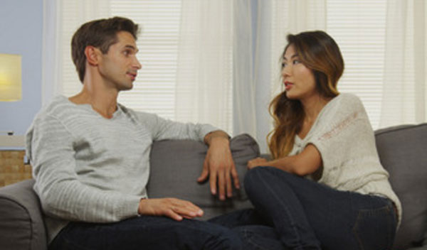 Парень с девушкой сидят на диване и ведут диалог