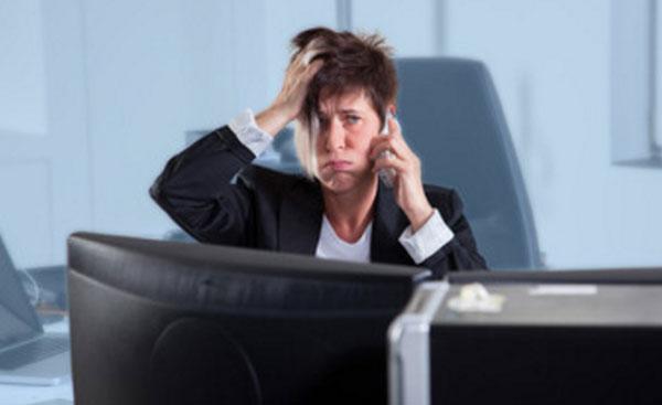 Замученная женщина говорит по телефону, сидя на работе за столом, перед компьютером
