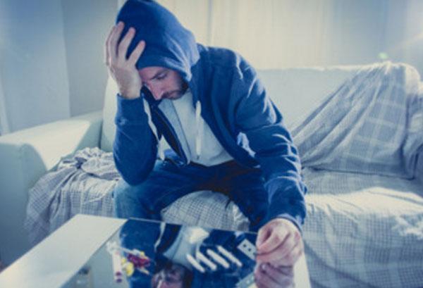Молодой человек в капюшоне держится за голову. Перед ним на столе наркотики