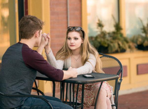 Девушка с парнем сидят за столиком и держатся за руки. Она пристально на него смотрит