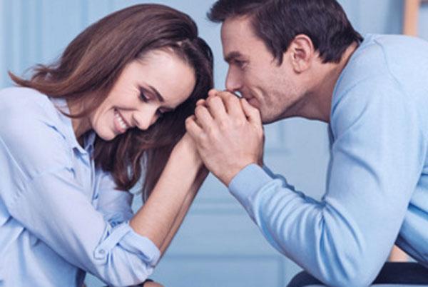 Мужчина с женщиной сидят лицом друг к другу. Он держит ее руки в своих и целует их