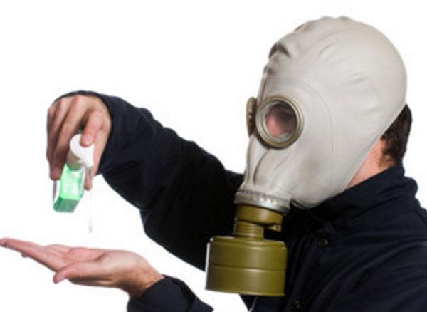 Мужчина в противогазе капает на руку дезинфицирующее средство