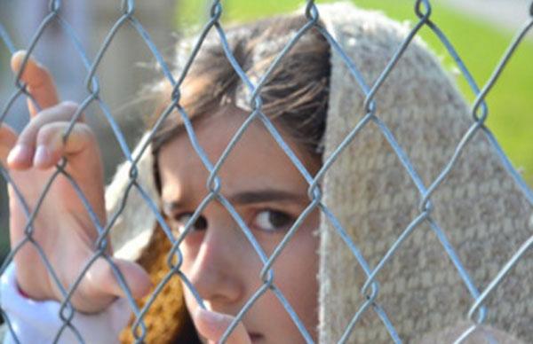 Напуганная девочка смотрит через прутья забора