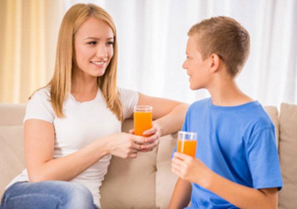 Мама общается с сыном. У обоих в руках стакан апельсинового сока