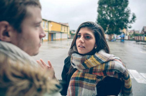 Девушка высказывает своему парню претензии, стоя на улице