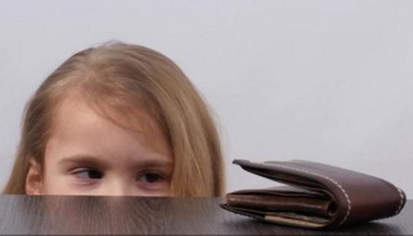 Девочка заинтересовано смотрит на кошелек, который лежит на столе