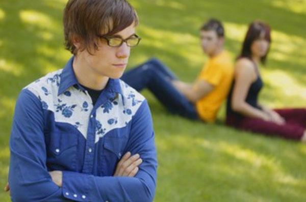 На переднем плане расстроенный, серьезный парень. на заднем парочка на траве, прислонились спинами