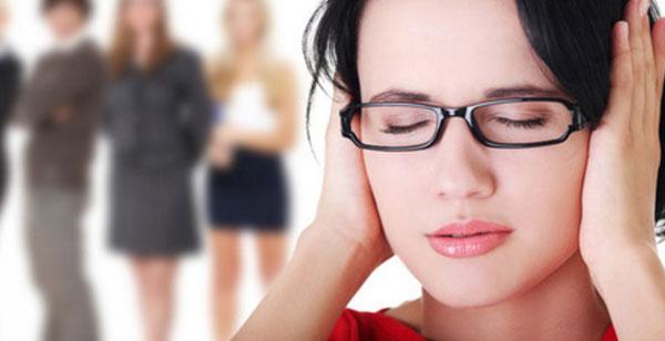 Женщина в очках с закрытыми глазами и ушами. На заднем плане стоят женщины