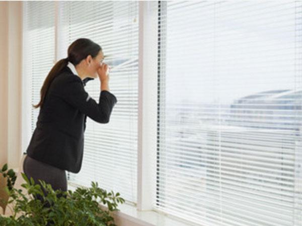 Женщина с опаской смотрит в окно через жалюзи