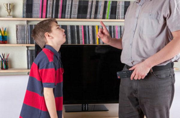 Папа стоит с пультом и что-то запрещает сыну