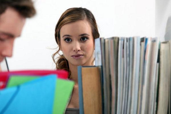 Девушка влюбленными глазами смотрит на парня, который стоит возле полки с книгами