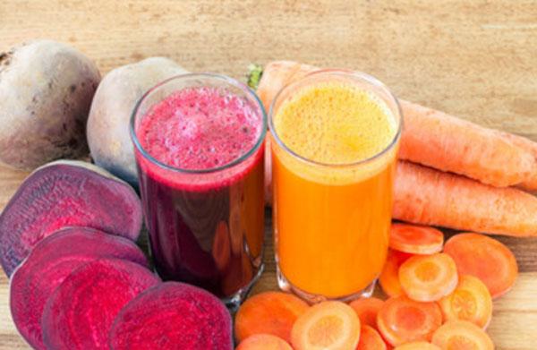 Два стакана с буряковым и свекольным соками. Рядом свекла и морковь, целые овощи и нарезанные кусочки