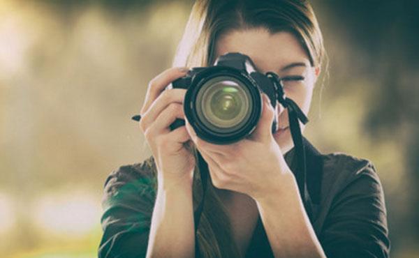 Девушка с фотоаппаратом делает снимок