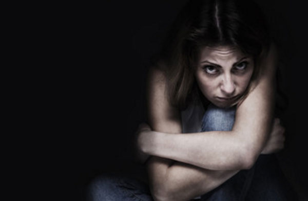 Скрученная женщина сидит в темноте