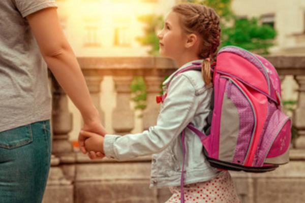 Девочка с рюкзаком на спине смотрит на маму заплаканными глазами