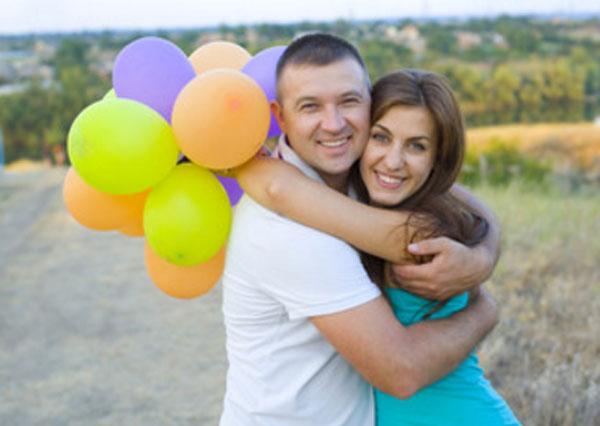 Парень с девушкой обнимают друг друга. Девушка держит шарики