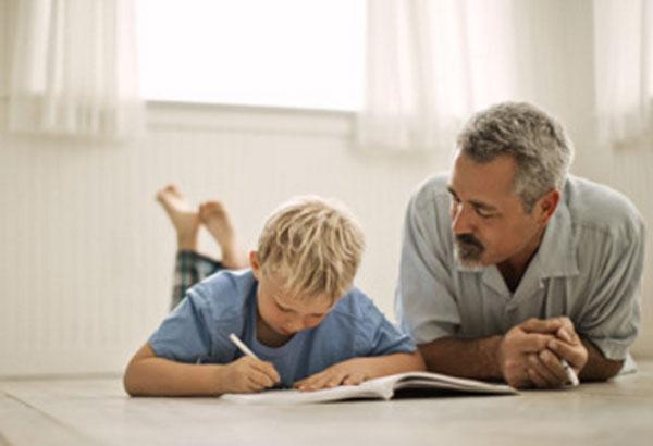 Отец с сыном лежат на полу. Мальчик что-что пишет