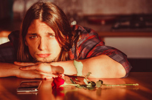 Грустный парень сидит за столом, опустил голову. На столе лежит роза и телефон