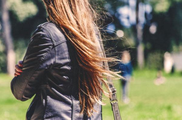 Женщина со сложенным руками идет по улице и смотрит в сторону человека, стоящего в далеке