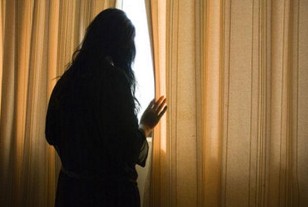 Женщина стоит возле зашторенного окна. С опаской выглядывает на улицу