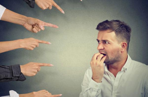В сторону мужчины тычут пальцами пять человек